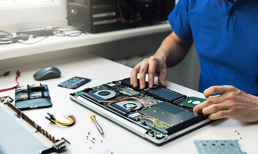 Photo of a man working on a laptop